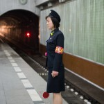The attendant's job is both to guide trains and to  protect and answer questions for the commuters.