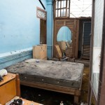 A bedroom is flooded because its roof was ripped off by the hurricane.