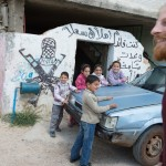 """The graffiti above the door reads """"Welcome"""" with image of resistance fighter/terrorist (depending on one's perspective) to the side."""