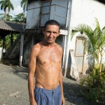 The proprieter of a cacao processing plant stands in front of his drying shed.