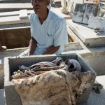 A cemetery worker sits by a osuary in Tomas Acea Cemetery in Cienfuegos.  Cuban tradition is that the dead are disinterred after the flesh is off the bone and the bones are reinterred.