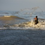 A man casts his fishing net into the surf in Bahia de Miel (Honey Bay) to supplement state-issued rations.