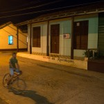 "A boy rides a bicycle in front of the Municipal Committee of Baracoa Headquarters with a painted sign that reads ""Woman is Revolution"""