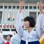 A woman dances under an image of the Great Leader Kim Il Sung, wearing a badge of Dear Leader Kim Jong Il, in mass folk dancing in front of Pyongyang Indoor Stadium.
