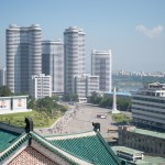 """This image is taken from the top of Grand People's Study Hall, looking out on a new neighborhood with high rises on the banks of the Taedong River. The obelisk in the center of the image is a Tower of Eternity - Yongsaengtap - a Monument to the Great Leaders Comrages Kim Jung Il and Kim Il Sung who """"will be with us forever.""""  This style of monument is found throughout the country."""