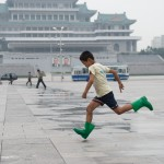 Running across Kim Il Sung Square with Grand People's Study Hall in the background, Pyongyang.
