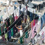 Man hanging clothes. Dhobi Ghat, world's largest outdoor laundry, Mumbai.